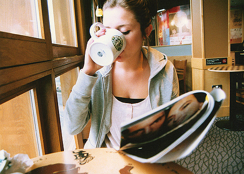 girl sipping starbucks mug reading beauty magazine